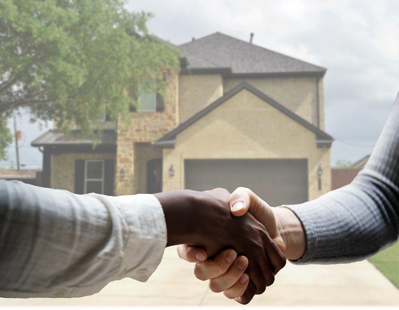 Imagem para artigo de crédito de habitação com imóvel no fundo e agente imobiliário com cliente