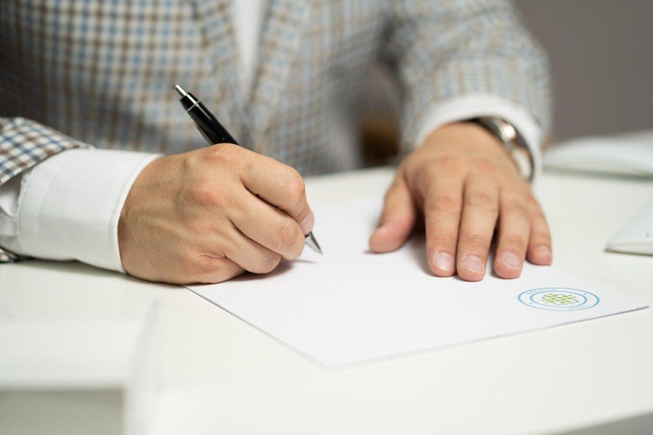 Imagem para artigo Contrato Aberto ou Exclusivo? com um homem de fato, a assinar um contrato