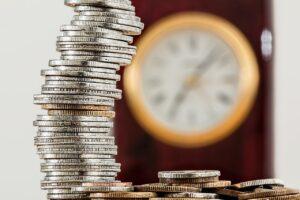 Imagem de um relógio e moedas para artigo de hipoteca ou penhora de imóveis